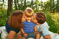 Happy parents kissing their child outdoors family Stock Photo