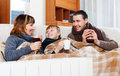 Happy parents and teenage son warming near warm calorifer with cups of tea in home Stock Photo