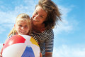 Happy parents and their child playing with a ball at the beach Royalty Free Stock Photo