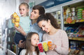 Happy parents with two kids holding purchases in store Royalty Free Stock Photo