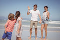 Happy parents waving hands while looking at children standing on shore Royalty Free Stock Photo