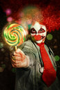 Happy party clown with lollies at circus carnival birthday giving out colorful entertainment performer Stock Photo