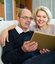 Happy pensioners watching old photoes in family album in room at home Royalty Free Stock Images