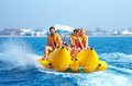 Happy people having fun on banana boat the yellow Royalty Free Stock Photography