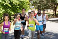 Happy people running race in park on a sunny day Royalty Free Stock Photography
