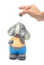 Happy piggy bank a hand putting some coin savings into a elephant Royalty Free Stock Photography
