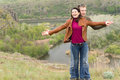 Happy playful attractive young couple rejoicing in the beauty of nature laughing as they stand with outstretched arms above a Royalty Free Stock Photography