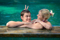 Happy playful couple relaxing in a swimming pool Royalty Free Stock Photography