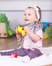 Happy playing baby girl sitting in her room Stock Images