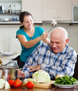 Happy playing mature couple cooking food with vegetables in home kitchen Stock Photography