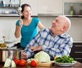 Happy playing mature couple in home kitchen cooking food Stock Images