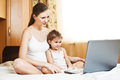 Happy pregnant mother and child with laptop Stock Images