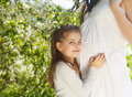 Happy pregnant mother and her little daughter in the spring day Royalty Free Stock Photo