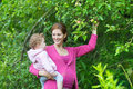 Happy pregnant mother and her one year old baby daughter young playing in apple garden Royalty Free Stock Photography