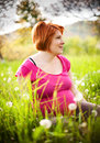 Happy pregnant mother sitting in grass and looking Royalty Free Stock Images