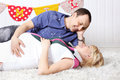 Happy pregnant wife and husband lie on carpet look at each other Royalty Free Stock Photos
