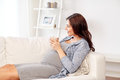 Happy pregnant woman with cup drinking tea at home Royalty Free Stock Photo