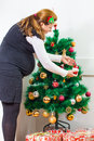 Happy pregnant woman decorate a Christmas tree Royalty Free Stock Photography