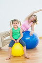 Happy pregnant woman exercising on exercise ball with young daughter women in a fitness studio Stock Photography