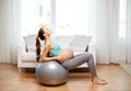 Happy pregnant woman exercising on fitball at home pregnancy sport fitness people and healthy lifestyle concept Royalty Free Stock Photography
