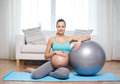 Happy pregnant woman with fitball at home pregnancy sport fitness people and healthy lifestyle concept exercising Royalty Free Stock Image