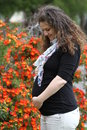 Happy pregnant woman in flowers looking her tummy Royalty Free Stock Photo