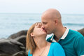 Happy pregnant woman and her husband kissing by the sea women summer Royalty Free Stock Photography
