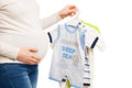 Happy pregnant woman holing clothes of child holding different items over white background Royalty Free Stock Photos