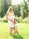 Happy pregnant woman, little child daughter hugging mother in summer Royalty Free Stock Photo