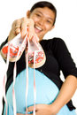Happy pregnant woman show a pair of baby shoes Stock Images