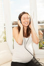Happy pregnant woman singing and listening to music Royalty Free Stock Photo