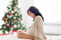 Happy pregnant woman sitting on bed at christmas Royalty Free Stock Photo
