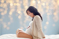 Happy pregnant woman sitting on bed
