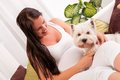 Happy pregnant woman with west highland white terrier relaxing on the sofa Royalty Free Stock Photo