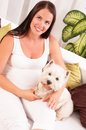 Happy pregnant woman with west highland white terrier relaxing on the sofa Stock Images