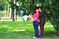 Happy pregnant woman women with her husband in the park Royalty Free Stock Photos
