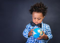 Happy preschooler discovering world african boy looking on little globe copy space geography lesson back to school concept Royalty Free Stock Photos