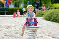 Happy preschooler girl having fun at playground little child adorable blonde toddler enjoying hot sunny summer day the bouncing on Royalty Free Stock Photos