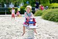 Happy preschooler girl having fun at playground little child adorable blonde toddler enjoying hot sunny summer day the bouncing on Royalty Free Stock Image