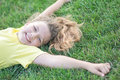 Happy pretty girl lying on green grass with outstretched arms and smiling at summer Royalty Free Stock Photo
