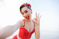 Happy pretty pinup girl in red swimsuit showing okay sign