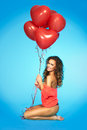 Happy pretty woman holding bunch of red air balloons at the studio