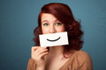 Happy pretty woman holding card with funny smiley on gradient background Stock Photos