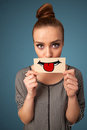 Happy pretty woman holding card with funny smiley on gradient background Stock Photo