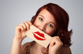 Happy pretty woman holding card with kiss lipstick mark on gradient background Royalty Free Stock Photo