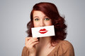 Happy pretty woman holding card with kiss lipstick mark on gradient background Royalty Free Stock Photos