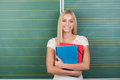 Happy pretty young female student with long blond her clutching her class notes in folders Royalty Free Stock Images