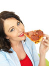 Happy Pretty Young Woman Eating a Slice of Freshly Baked Pepperoni and Ham Pizza Royalty Free Stock Photo