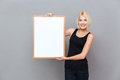 Happy pretty young woman holding blank white board Royalty Free Stock Photo
