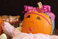 Happy pumpkin baby with presents a dressed up as a princess next to pink Stock Photo